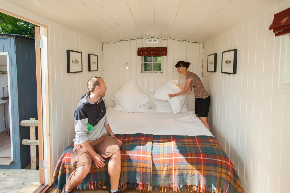 Couple making the bed at Meon Springs Shepherd's Huts