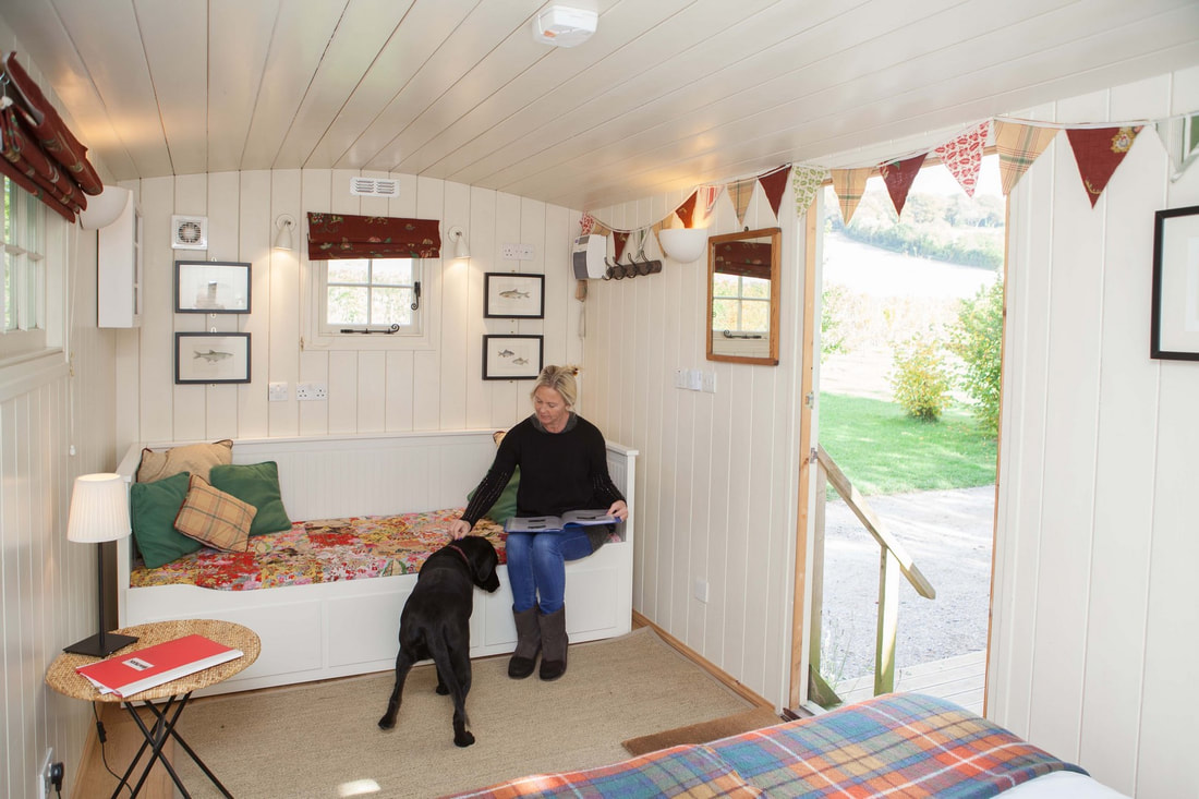 Shepherd's Hut interior, lady with dog